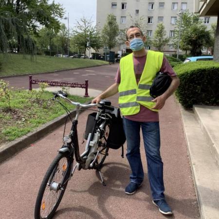 Mathias pose à côté du vélo municipal, masqué et habillé d'un gilet jaune, avec son casque sous le bras.